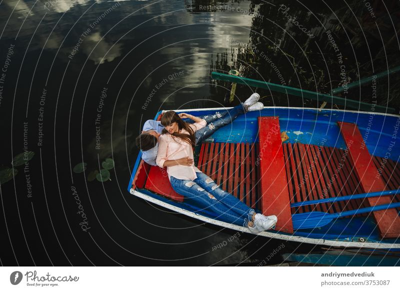 Liebespaar im Boot. Draufsicht auf ein schönes junges Paar, das sich umarmt und lächelt, während es im Boot liegt. Wasser See reisen Zwei Personen Abenteuer
