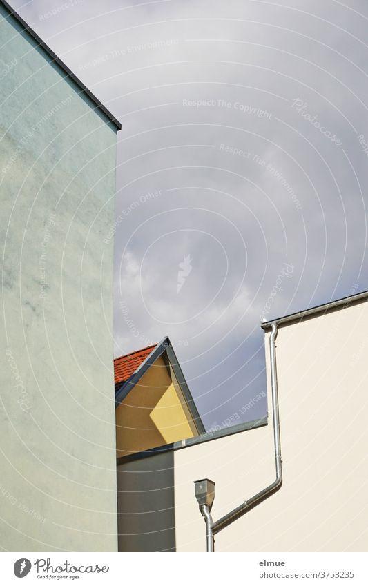 Formen- und Linienmix aus verschieden farbigen Häuserwänden mit Dachrinne und Fallrohr vor bewölktem Himmel, Schatten werfend Haus Farbe Giebel Hausgiebel Wand