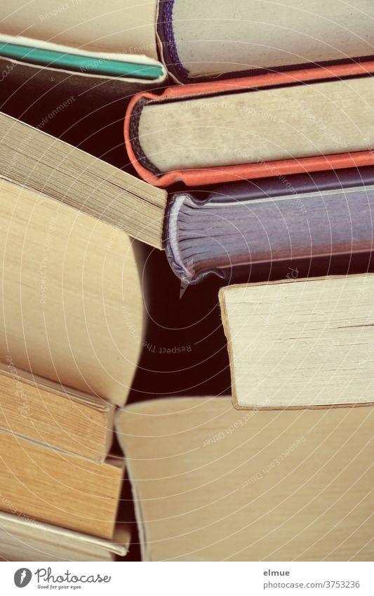 zwei Stapel unterschiedlicher, gebrauchter Bücher stützen sich gegenseitig Buch lesen Büchersammlung Bildung Lesestoff Ansammlung lernen Bibliothek Literatur