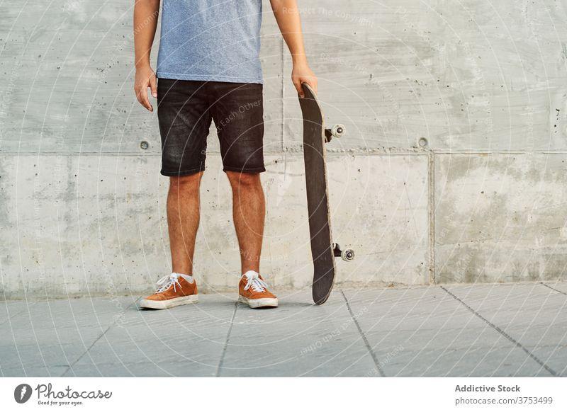 Crop Skater stehend auf der Straße Mann Skateboard Großstadt Streetstyle trendy Outfit urban Gebäude männlich Straßenbelag Bürgersteig modern Stil Zeitgenosse
