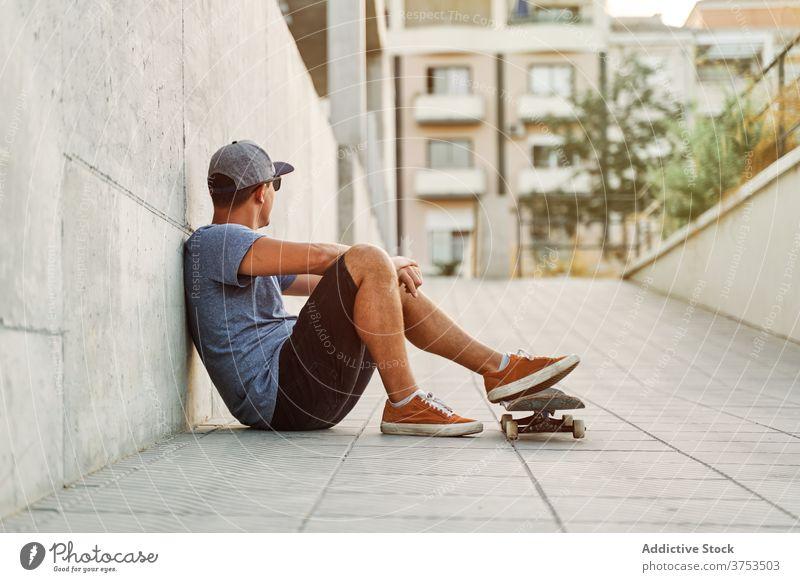 Stilvoller Mann mit Skateboard in der Stadt Skater urban Gebäude Hobby Fähigkeit fettarm Wand männlich Outfit selbstbewusst trendy Straße modern jung Großstadt