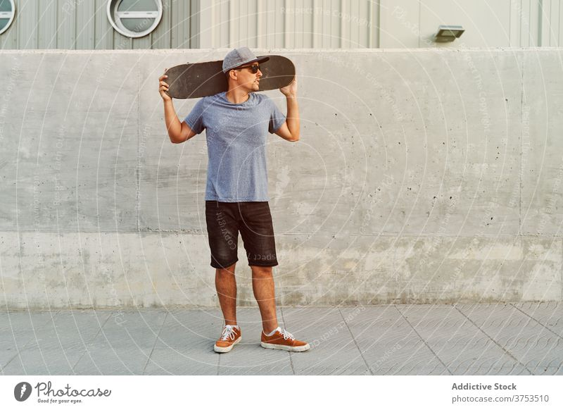 Selbstbewusster Mann mit Skateboard in der Nähe des Gebäudes Großstadt Skater Bestimmen Sie Stil Hobby trendy urban Straße männlich Sonnenbrille Outfit modern