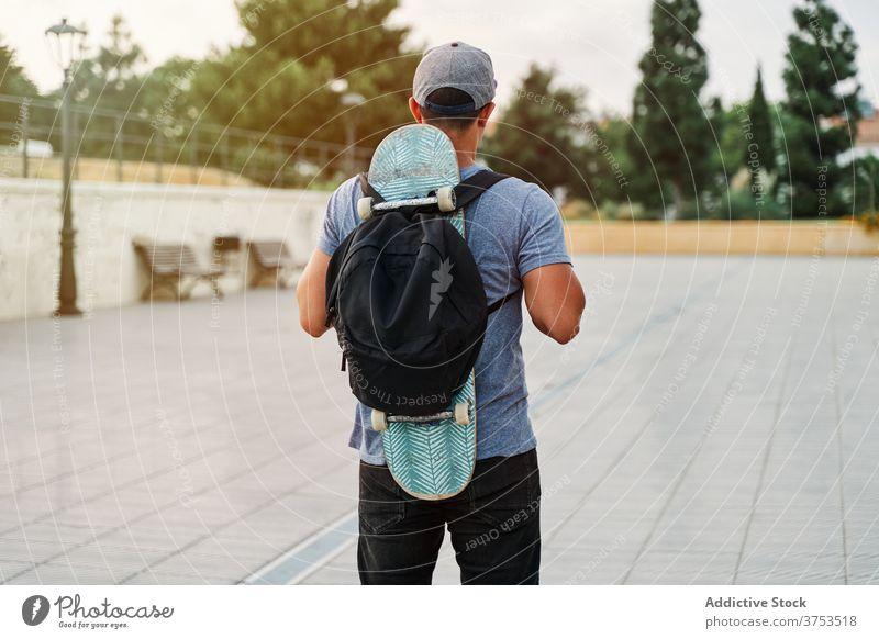 Unbekannter Mann mit Skateboard und Rucksack in der Stadt Skater Großstadt Straße urban Stil Fähigkeit Hobby männlich alt Hipster cool stehen trendy modern