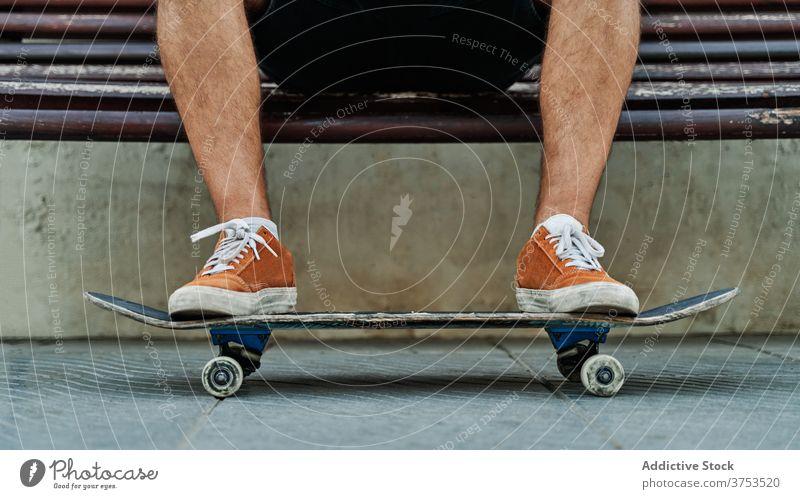 Crop Skater sitzen auf Bank in der Stadt urban Skateboard Mann sich[Akk] entspannen Stil Straße cool Generation männlich jung schäbig hölzern Großstadt ruhen