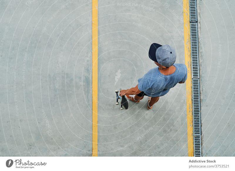 Mann mit Skateboard auf der Straße stehend Skater Großstadt urban Streetstyle trendy Asphalt Hobby männlich cool Sommer modern Freiheit Straßenbelag Kultur Stil