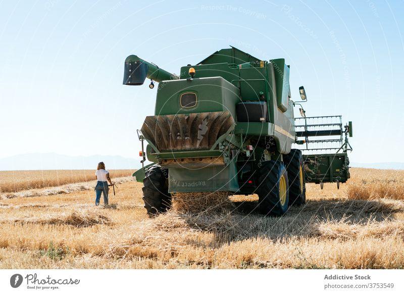 Frau in der Nähe von Mähdrescher im Feld Ernte Maschine Ackerbau Weizen Landwirt Gerät Korn Industrie ländlich riesig Natur Sommer Pflanze organisch Wachstum