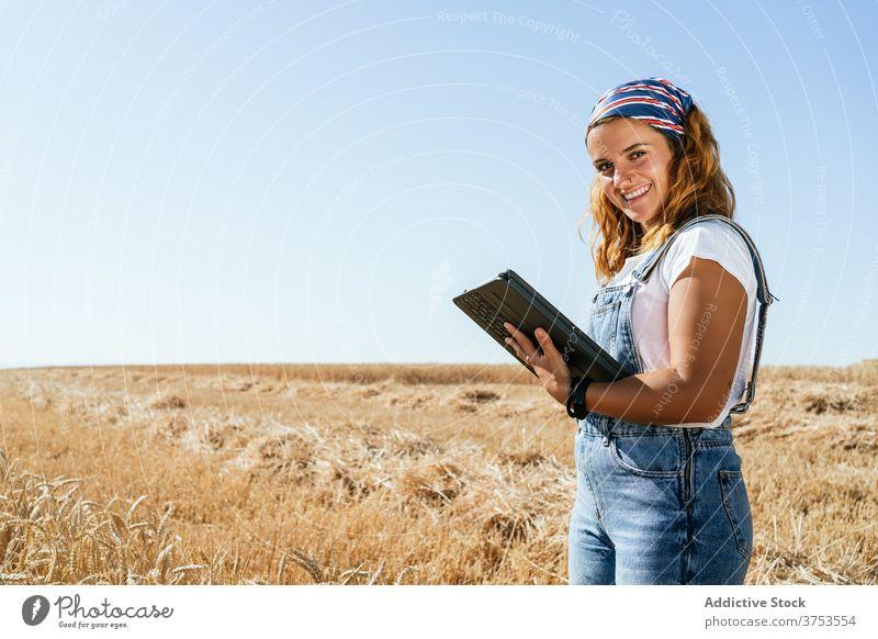 Lächelnde Frau mit Tablet im Feld Landwirt Weizen Tablette Browsen benutzend Ackerbau Landschaft ländlich Apparatur Gerät Sommer Natur Wiese Schonung Ackerland