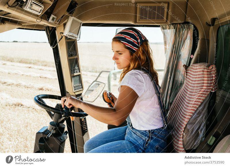 Fokussierte Frau bei der Bedienung einer landwirtschaftlichen Maschine Bauernhof Mähdrescher Ernte arbeiten abholen Saison Feld Ackerbau Weizen ländlich Job