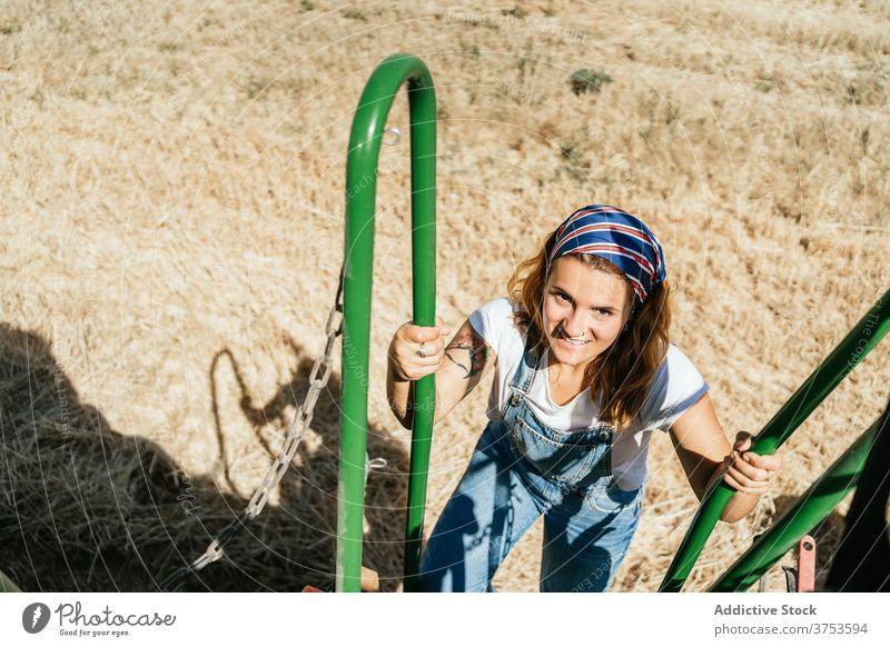 Frau auf den Stufen eines Mähdreschers Maschine Ernte Feld Landwirt Schritt Weizen Landschaft Verkehr Sommer Natur Ackerbau Bauernhof ländlich Saison Pflanze