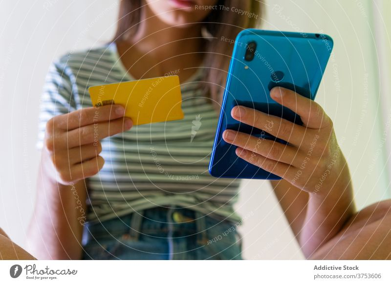 Frau bei der Online-Zahlung per Smartphone online Werkstatt Plastikkarte heimwärts Orden Kauf benutzend bezahlen Postkarte Funktelefon Gerät Käufer konsumgeil