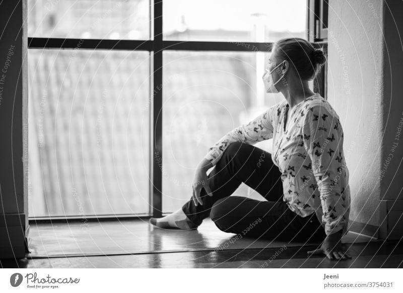 Frau mit Mund-Nasen-Schutz blickt einsam und isoliert aus dem Fenster I corona thoughts Corona Coronavirus Corona-Pandemie Schutzmaske Mundschutz Covid-19