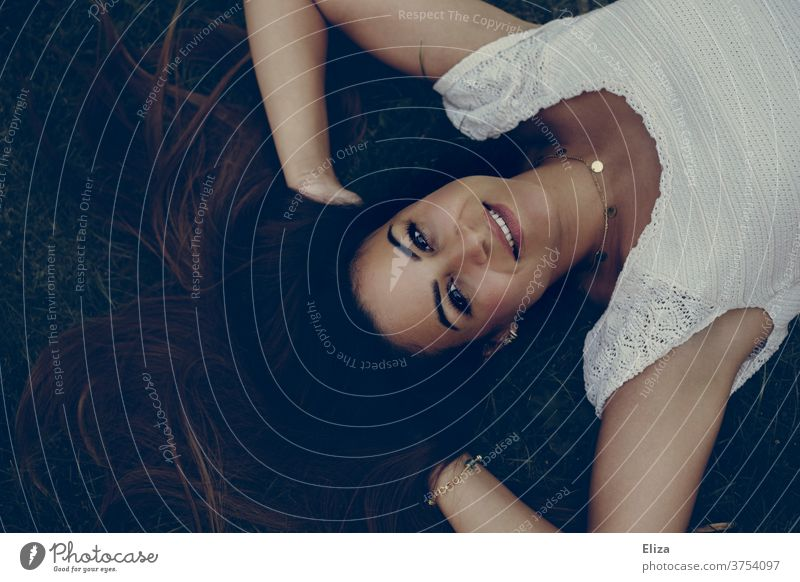 Junge dunkelhaarige Frau liegt auf dem Boden mit den Händen in den Haaren und blickt strahlend nach oben in die Kamera junge Frau braunhaarig Beautyfotografie