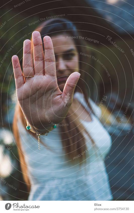 Eine junge Frau symbolisiert Stopp indem sie ihre Hand vor sich ausstreckt. Nein heißt Nein. Halt wehrhaft Ablehnung Gefühle Signal Kommunikation wehren