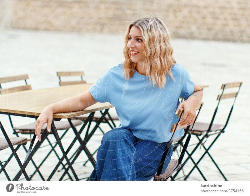 Junge Frauen in T-Shirt und Jeans sitzen in einem Straßencafé jung Mädchen anhaben Attrappe Jeanshose sitzt Café Tisch Rundhals Bekleidungsmockup lässig Sitz
