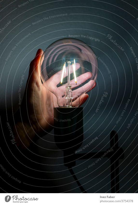 Person, die eine LED-Glühbirne hält, fängt das Licht Hand Knolle Konzept Idee Technik & Technologie Energie Erde Globus Leuchtdiode LED-Leuchte LED-Lampe