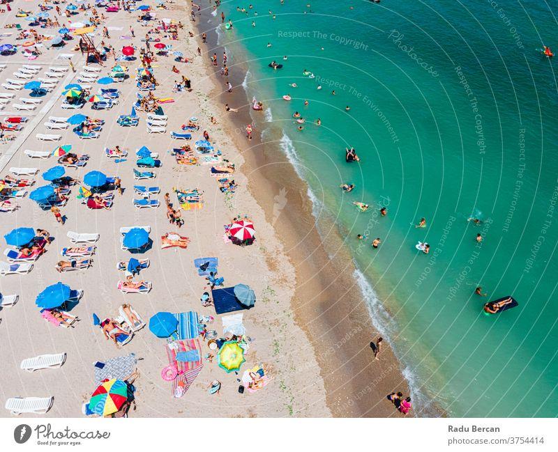 Luftaufnahme von Menschen und bunten Regenschirmen am Strand des Ozeans im Sommer Antenne Ansicht Sand Hintergrund Wasser MEER Urlaub blau reisen mediterran