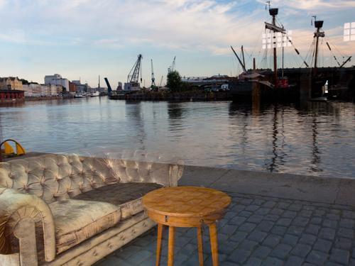Ein Sofa mit Tisch steht am Kai des Lübecker Hafens. Täuschende Spiegelung in einer Fensterscheibe Reflexion & Spiegelung Schiffe Kräne Hafenanlage Täuschung