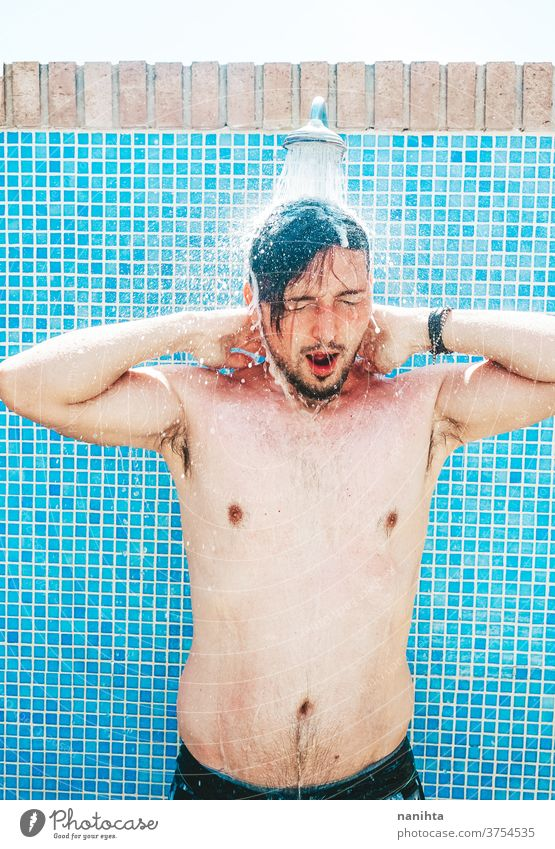 Junger Mann duscht vor dem Schwimmbad - ein lizenzfreies
