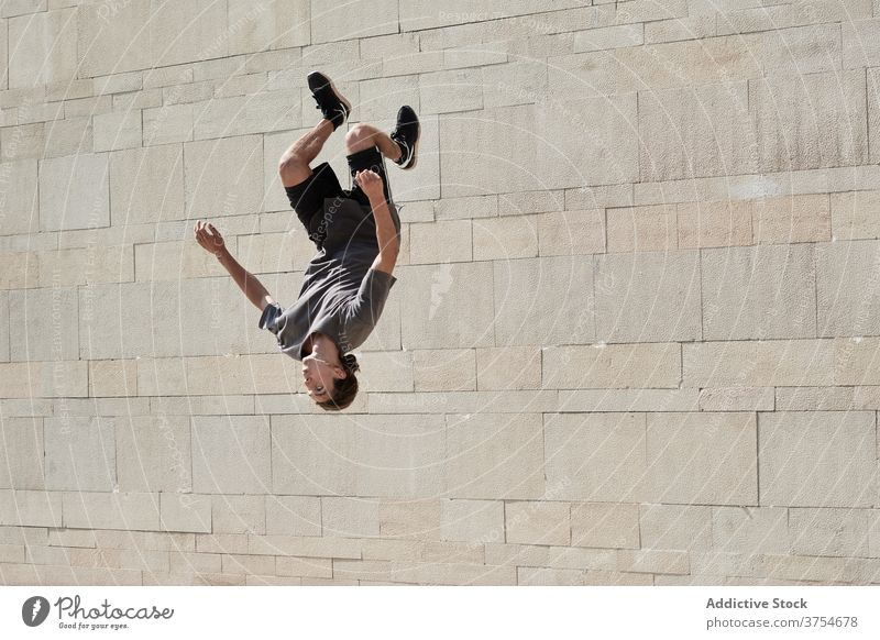 Mann macht Rückwärtssalto in der Stadt Le Parkour Überschlag springen akrobatisch Stunt Trick urban aktiv männlich Energie Sommer üben Übung