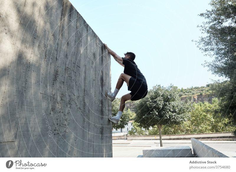 Starker Mann springt auf Gebäudemauer Le Parkour springen Stunt Freestyle Wand Trick urban Großstadt extrem Gefahr männlich Straße Mut jung aktiv gutaussehend