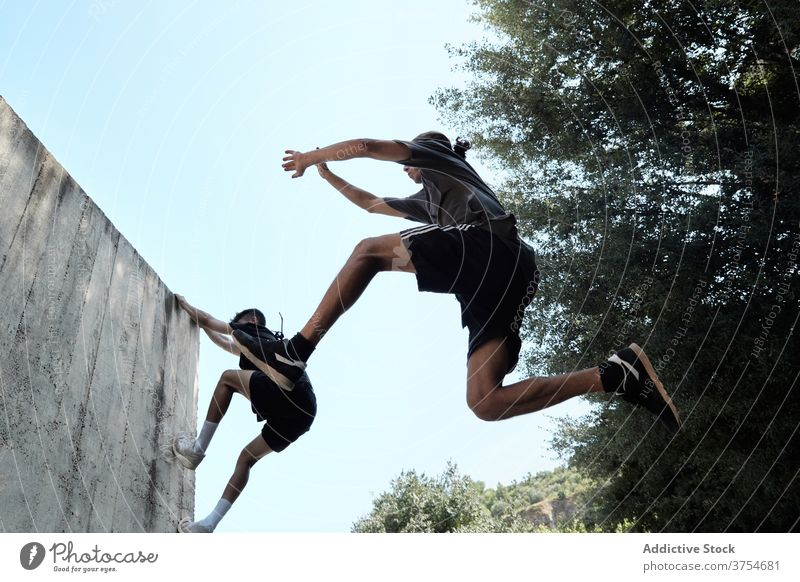 Männer springen in der Stadt über den Boden Le Parkour Stunt Trick Großstadt urban extrem Gefahr Hobby männlich Mut aktiv gutaussehend Aktivität professionell