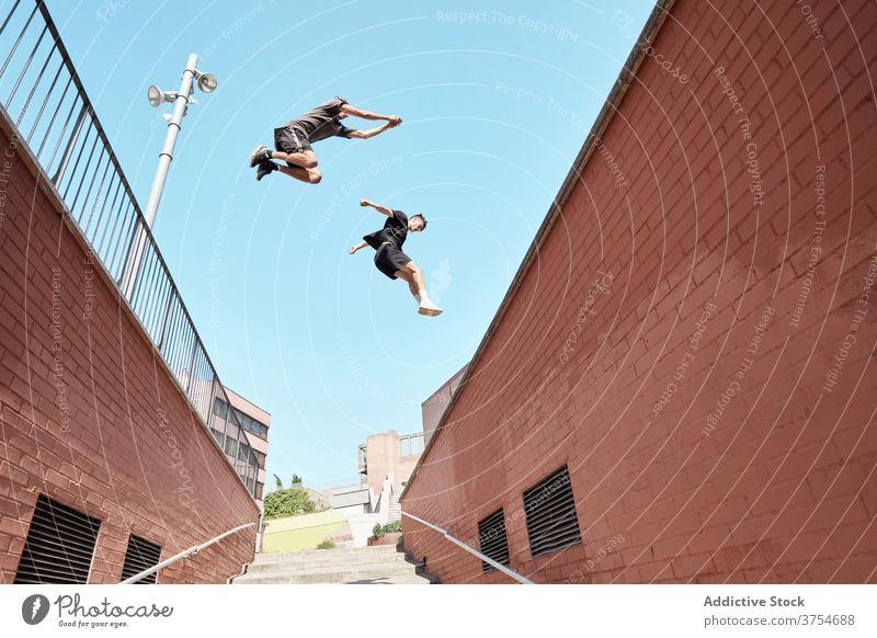 Männer springen über eine Treppe in der Stadt Le Parkour Stunt Trick Großstadt Zusammensein Treppenhaus urban extrem Gefahr Hobby Mut aktiv Aktivität