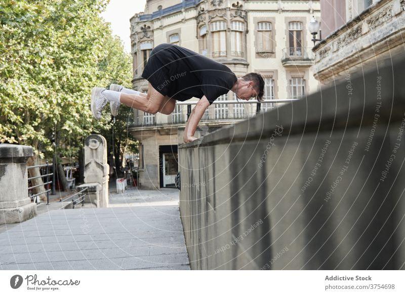 Starker Mann macht Parkour auf der Straße springen Le Parkour Hindernis Stunt Trick Gleichgewicht urban Adrenalin extrem männlich Großstadt Hobby Mut aktiv