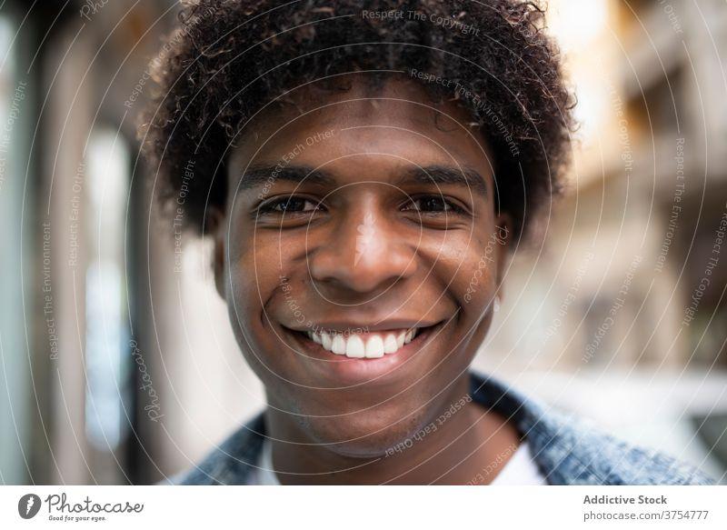 Erfreuter ethnischer Mann schaut in die Kamera Freude Porträt Lächeln gutaussehend charismatisch Großstadt Afro-Look Frisur Vorschein männlich schwarz