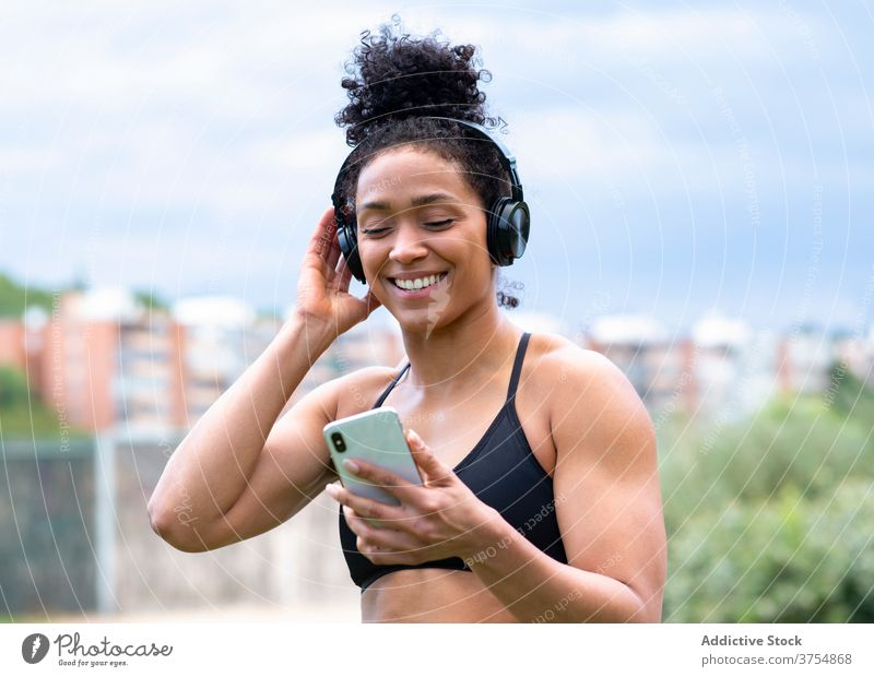 Zufriedene Sportlerin, die mit Kopfhörern Musik hört zuhören Training genießen Athlet passen Freude Smartphone Frau ethnisch schwarz BH Großstadt Drahtlos