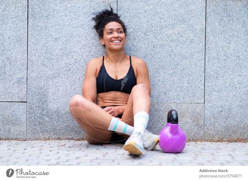 Inhalt ethnische Sportlerin ruht sich während des Trainings aus operativ sich[Akk] entspannen Pause Großstadt Kettlebell Lächeln passen Frau schwarz