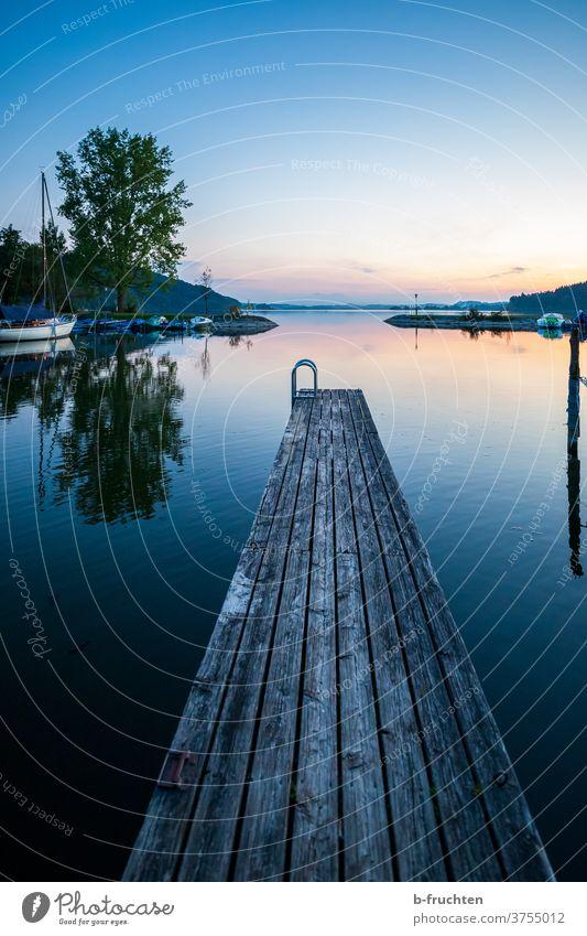 kleiner Holzsteg im Abendlicht Abendstimmung Natur Außenaufnahme Landschaft Himmel Sonnenuntergang Abenddämmerung Menschenleer Wasser Steg See Boote Segelboote