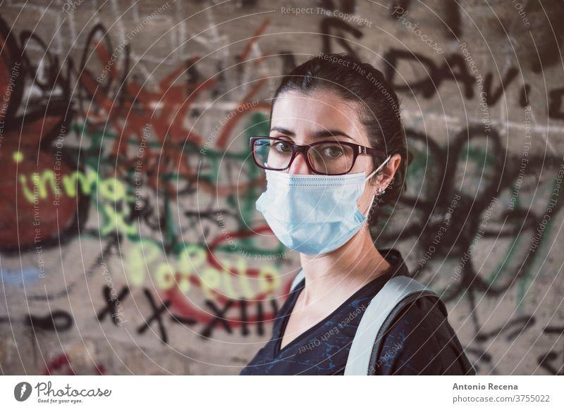 Frau im Kamerablick mit Gesichtsmaske auf Stadtfoto Frauen Bund 19 Graffiti Person Menschen 30s 30-34 Jahre 30-39 Jahre Rucksack laufen wandern Brille Pandemie