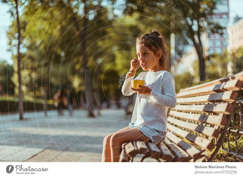 Lateinamerikanisches Kind, das auf einer Parkbank mit schönen Bäumen im Hintergrund sitzt. Sie isst gerade ein Eis. außerhalb wirklich Glück Sonnenuntergang
