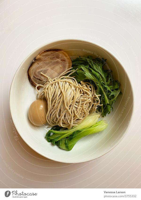 Schweinefleisch-Ramen-Zutaten in weißer Schüssel ohne Brühe. Ramennudeln Suppe Lebensmittel diy selbstgemacht Japanisches Essen Ei Nudeln Bok Choi
