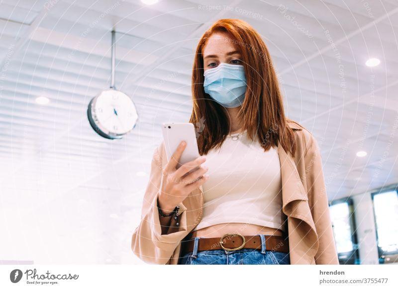 Frau mit Maske, die ihr Smartphone am Bahnhof benutzt Öffentlich Reise Tourist Ausflug Zug reisend Wirtschaft Virus Coronavirus Seuche Pandemie Mundschutz