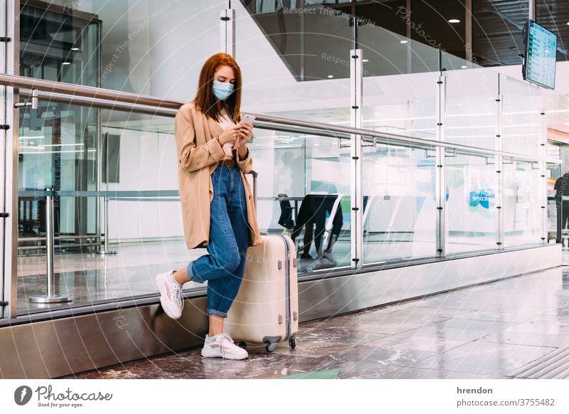 Frau mit einer Maske, die am Bahnhof mit ihrem Smartphone eine Textnachricht sendet Geschäftsfrau Anruf Arbeit Warten Transport Verkehr Öffentlich Reise Tourist