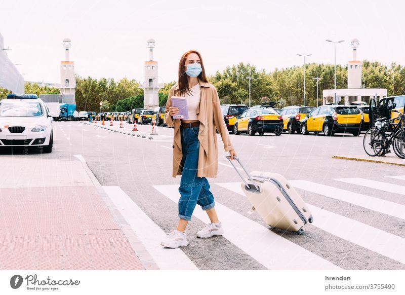 junge Frau mit Gesichtsmaske überquert die Straße, um ein Taxi aus dem Bahnhof zu nehmen Coronavirus Tourismus Transport Tourist Verkehr Öffentlich Reise