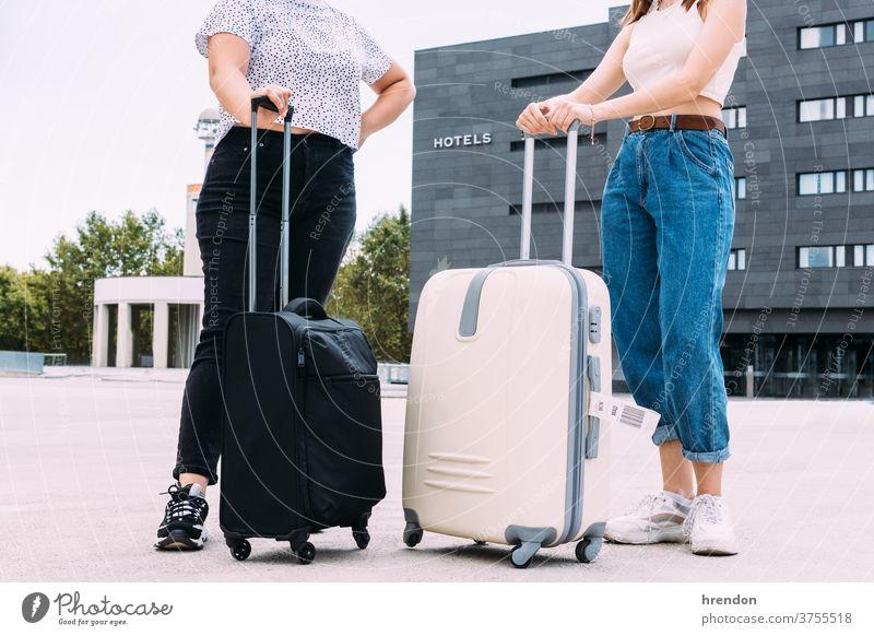 zwei nicht erkennbare Touristen mit ihrem Gepäck vor dem Hotel, in dem sie übernachten werden Hotels Geisel Tourismus Ferien Verkehr Öffentlich Reise Ausflug