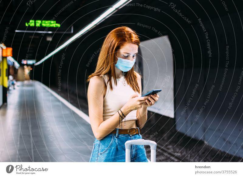 junge Frau mit Gesichtsmaske überprüft ihr Smartphone, während sie auf die U-Bahn wartet Transport Verkehr Öffentlich Reise Tourist Ausflug Pendler Arbeitsweg