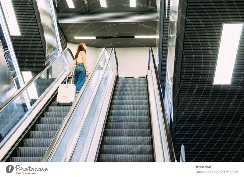 junger Tourist mit Gesichtsmaske benutzt U-Bahn-Rolltreppe Treppenhaus Terminal Coronavirus Tourismus Transport Verkehr Öffentlich Reise Ausflug Pendler