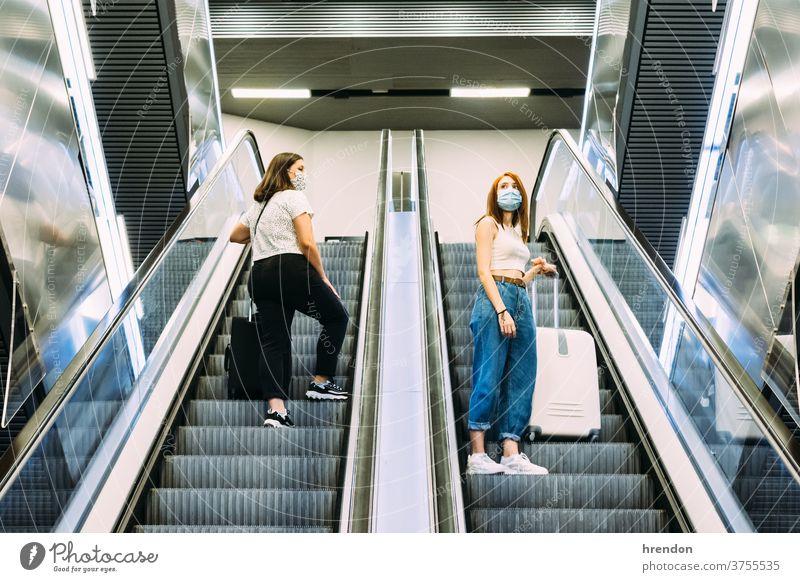 zwei junge Touristen mit Gesichtsmasken die U-Bahn-Rolltreppen benutzen Treppenhaus Terminal Coronavirus Tourismus Transport Verkehr Öffentlich Reise Ausflug