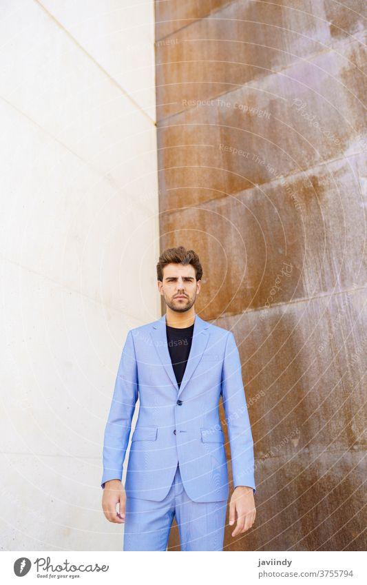 Attraktiver Mann im Anzug, der im städtischen Hintergrund steht. tausendjährig Mode Frisur Geschäftsmann Business männlich urban jung Lifestyle im Freien modern