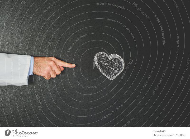 Arzt zeigt auf ein Herz Kardiologe Kardiologie zeigen deuten herzinfakt Gesundheit Medizin Krankheit Gesundheitswesen