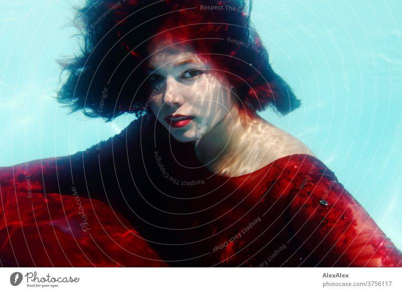 Junge Frau in rotem Ballkleid taucht in einem Swimming Pool junge Frau Mädchen schön anmutig sportlich Sonnenlicht Sommer Swimmingpool Schwimmbecken Wasser