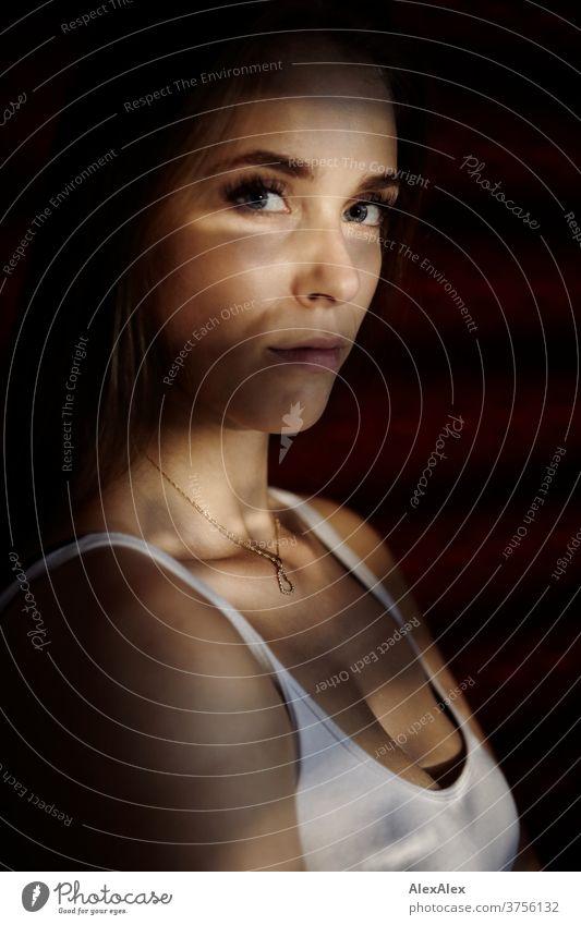 Dunkles Portrait einer jungen Frau mit Lichtsteifen durch die Jalousie Tag Ästhetik fokussiert Kraft Dekolleté groß bestimmt ruhig athletisch Haut einzigartig