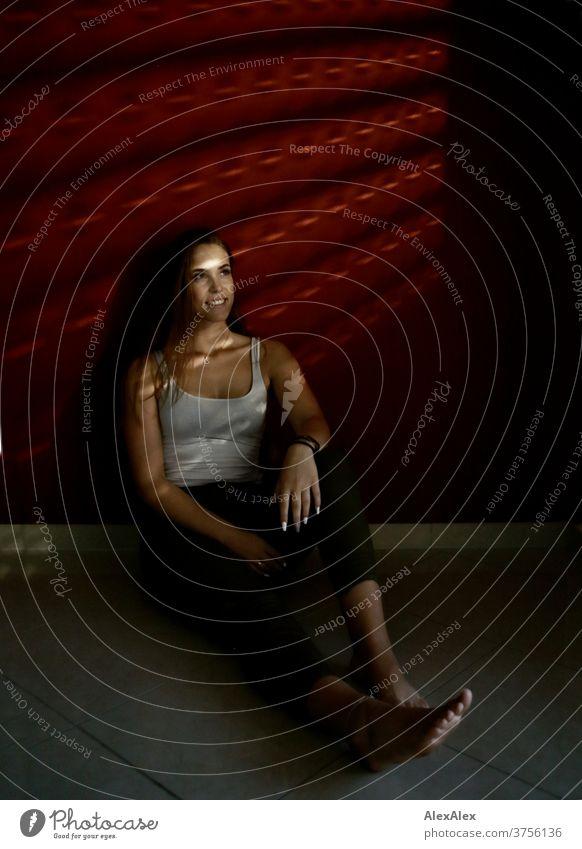 Dunkles Portrait einer jungen Frau vor roter Wand mit Lichtsteifen durch die Jalousie Tag Ästhetik fokussiert Kraft Dekolleté groß bestimmt ruhig athletisch