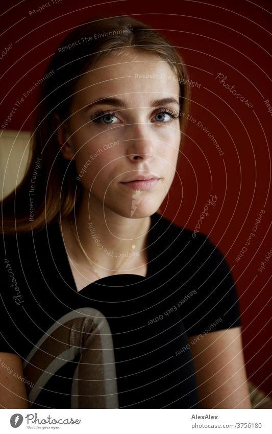 Junge Frau auf beigem Sessel vor roter Wand Tag Ästhetik fokussiert Kraft blaue augen Dekolleté groß bestimmt ruhig athletisch Haut einzigartig weiblich