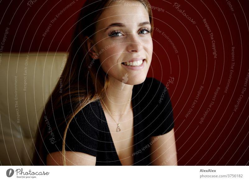 Junge Frau auf beigem Sessel vor roter Wand lächelt lächeln Freude Tag Ästhetik fokussiert Kraft blaue augen Dekolleté groß bestimmt ruhig athletisch Haut