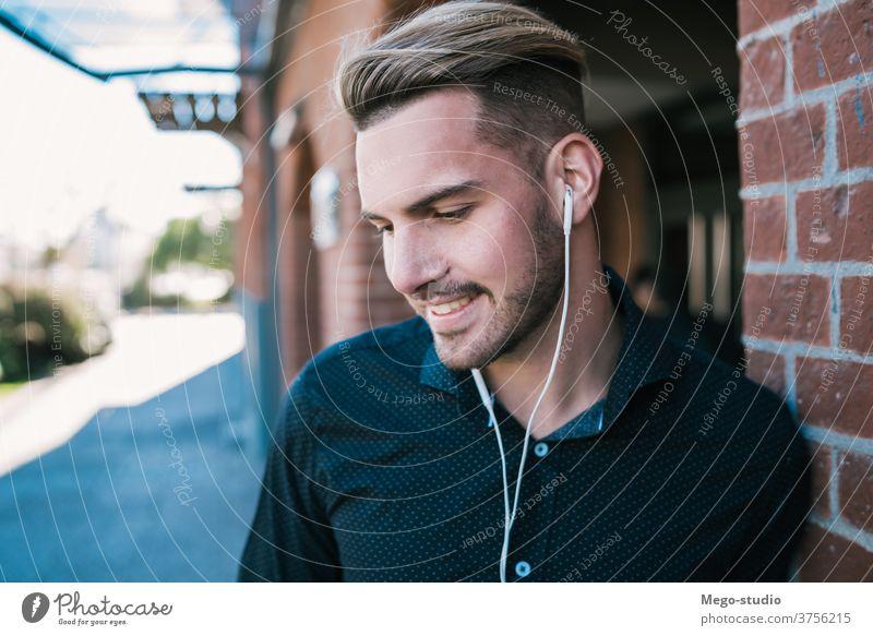 Mann, der mit Kopfhörern Musik hört. Person jung zuhören Menschen Erwachsener Apparatur im Freien Technik & Technologie Lifestyle männlich lässig allein Klang