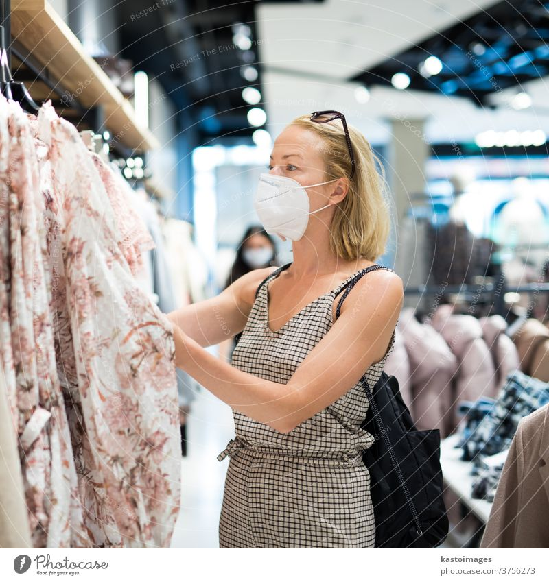 Modische Frau mit Gesichtsschutzmaske trägt Einkaufskleidung im wiedereröffneten Einzelhandelsgeschäft. Neuer normaler Lebensstil während einer Coronavirus-Pandemie